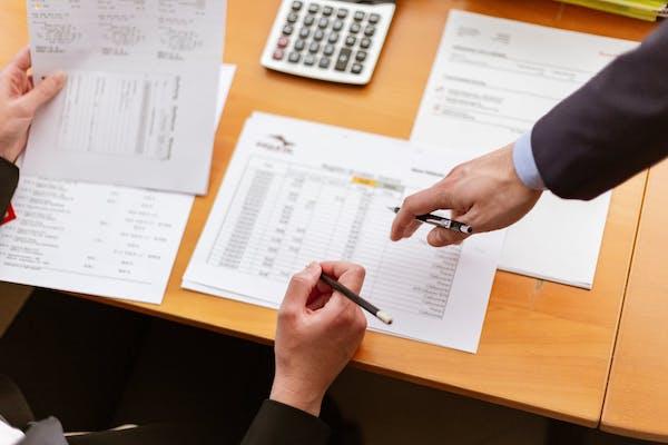 ufficio, mani indicano calcoli - calcolo degli indici della crisi di impresa