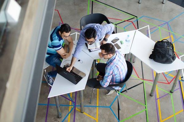 ragazzi lavorano attorno a un tavolo - ch calcola gli indici della crisi di impresa